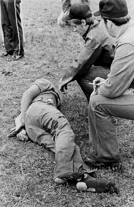 The Missouri Water Patrol sharpshooter (center) kneels at a fugitive's side minutes after felling him with a single shot from across a field.