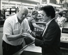 Teddy handles the household finances including having the grocery store cashier use her finger to write the total in his hand. (Copyright by John S. Stewart/LEFTeyeSTORIES.com)
