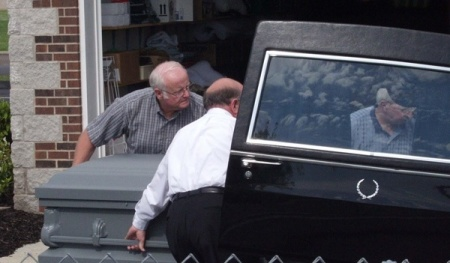 Funeral home personnel and members of the Gotti entourage load an empty casket into a hearse as a decoy for the media who hoped to photograph it being loaded onto a plane for the trip to New York (Photo Copyright by John S. Stewart/LEFTeyeSTORIES.com)